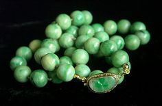 This is an amazing necklace with Chinese antique jadeite jade beads and a beautiful silver gilted carved jade clasp and 14K gold beads. The jadeite jade beads are of even sizes that are very hard to find. All jade beads and the carved jade in the clasp are natural without treatment - GRADE A.