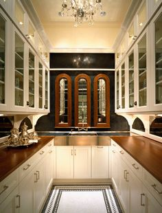 Another beautiful butler's pantry by Mick De Giulio. Maple countertops, polished nickel sink, modern cabinets, crystal chandelier.