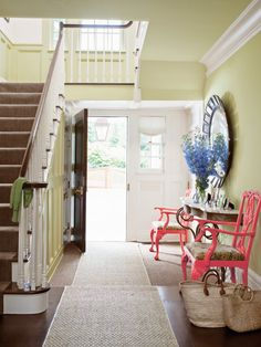 The walls and wainscotting of this entryway are painted Benjamin Moore's Castleton Mist, while the chairs are coated in Coral Essence. #countryliving