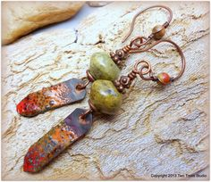 """Chunky (12 mm) rondelles of speckled olive/beige ocean jasper are paired with torch-fired enameled copper """"matchsticks"""" in fiery red and orange with a hint of olive. By Two Trees Studio, $37.00."""