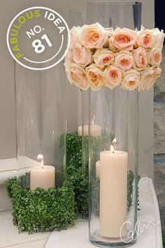 Tall glass hurricanes wrapped in spring greens and light pink roses hold a single pillar candle.