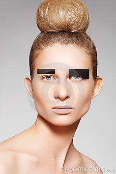 Fashion model with creative make-up, bun hairstyle by Seprimoris, via Dreamstime