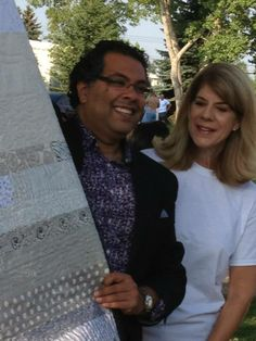 Quilting for Calgary founder Bev Rogan presents Mayor Nenshi with his own nap time quilt.