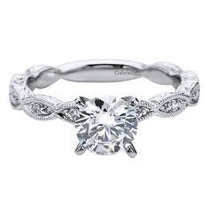 Gabriel & Co. ER4122W44JJ 14k White Gold Diamond Ribbon Engagement Ring Hand cut etching on the band of this Gabriel & Co. Diamond Engagement ring give off a stunning luminous shine and eff…