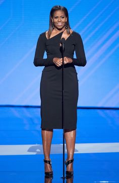 Michelle Obama stunned at the 2017 ESPY Awards, wearing a figure-skimming LBD with an alternative neckline. Obama kept it classic yet modern with Jennifer Fisher statement earrings, stacked Hearts on Fire diamond rings, and strappy black pumps. Michelle Obama Fashion, Michelle And Barack Obama, Presidente Obama, Nice Dresses, Dresses For Work, Beautiful Dresses, Celebrity Look, Celebrity Babies, Celebrity Quotes
