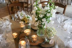 Rustic centerpiece with wooden rounds, flowers in mason jars, burlap table runner, mercury candle holders