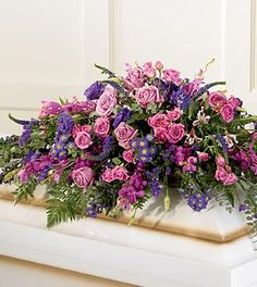 The Blanket of Flowers Casket Spray is abundantly made of jewel-toned pink and purple blooms. Hot pink and lavender roses, fuchsia orchids, purple lisianthus, purple Veronica and purple statice are accented with baby blue eucalyptus for a stunning blanket of flowers for your loved one.
