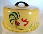 Vintage metal cake carrier with a stylized rooster design.