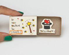 Schattig leuk aanmoediging kaart Matchbox - als je In Magic gelooft, u vindt het  Deze aanbieding is voor één matchbox. Dit is een geweldig alternatief voor een traditionele wenskaart. Verras uw dierbaren met een schattig privébericht verborgen in deze mooi ingerichte luciferdoosjes!  Elk item wordt met de hand gemaakt van een echte matchbox. De ontwerpen zijn hand getrokken, gedrukt op papier en vervolgens de hand geassembleerd zodat elke individuele matchbox die speciale persoonlijke…
