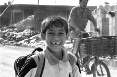 Baghdad in 2011, a boy going to school with a smile for the camera. #Photography #Iraq #Baghdad #black and white #Documentary #People