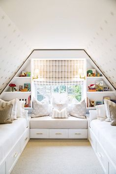 Neutral kids bedroom with window seat and twin beds, peaked roof