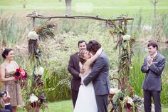 Sweet almost kiss photo during the outdoor ceremony at the Round Barn wedding venue in central Vermont... Love the rustic wood arch with wildflowers!