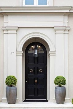So french - glossy black front door with twin topiaries. Perfectly manicured of course...