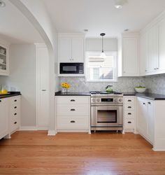 kitchen with pale gray walls framing white cabinets painted Benjamin Moore Simply White paired with honed Absolute Black Granite countertops with ogee edge and statuary white marble herringbone backsplash.