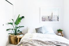 Serene bedroom with New York City photograph print and indoor plant.