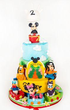 Clubul lui Mickey Mouse, cu cele mai vesele figurine Disney, sunt detaliile ce decoreaza un tort delicios, pregatit special pentru cea mai frumoasa petrecere organizata de tine pentru micutul tau. Mickey Mouse, Mai, Birthday Cake, Disney, Desserts, Food, Tailgate Desserts, Deserts, Birthday Cakes