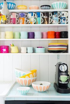 Super pretty colorful mugs + bowls on open kitchen shelves