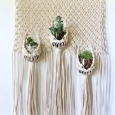 This large, white macrame hanging planter panel wants to hold all your favorite succulents and air plants in the cups of its pouches. Your plant friends need plenty of sunshine and knotty hugs, and this fun, original piece of macrame knows it. Both beautiful and functional, this hand-knotted macrame panel was inspired by vintage pieces and reimagined for the modern bohemian or minimalist space. A show-stopper of a housewarming present or a one-of-a-kind treat for yourself. Vintage or…