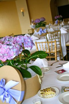 Pretty and proper centerpieces for a luncheon. Kraft hat boxes with potted hydrangea, a satin bow, and pearl strands. www.rsvpfloral.com