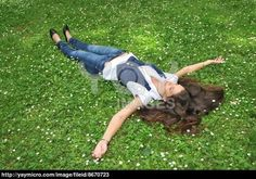 lying on the lawn | Royalty Free Image of Young Woman Lying In Grass With Flowers