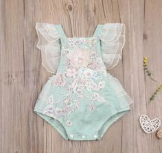 Eloise Green & Pink Vintage Embroidered Floral Birthday Tutu Romper This beautiful seafoam green tutu romper showcases delicate embroidered detailing through the bodice with a blush floral motif 3D design. Ruffled gauze detailing along the shoulders, sides, and bum creates the sweetest ruffle bum romper. Great for a first birthday shoot, or a summer soiree!