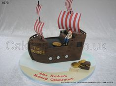 Pirate Ship Cake. Ahaar.... Large pirate galleon shaped novelty cake on a sea and sand covered board. Complimented with a modelled pirate and treasure chest filled with sweet coins