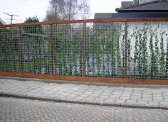 Erfafscheiding van betongaas gecombineerd met hardhouten ruwe planken en palen.