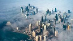 Qatar row: Six countries cut links with Doha - An aerial view of high-rise buildings emerging through fog covering the skyline of Doha