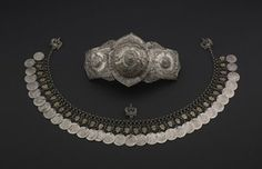 A woman's silver plated belt clasp ('pafta' or 'kolen'), in two parts, with an embossed and chased central boss extending into pointed ogee shapes at top and bottom, flanked by two rectangular side panels, the central boss attached to one of the side panels. Decorated with repoussé foliate ornament. Fastened with hook and eye.