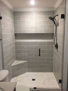 "Our finished walk-in shower.   Walls: Florim USA 6x24 (cut in half) ""Layers"" tiles in Sediment;  Shower floor & back of the shelf: Florim USA ""Luxury"" hexagon mosaic tiles in Calacatta;  Glass door/wall: Glass Warehouse 78""x57.5"" Frameless Hinged w/ rubbed bronze fixtures;  Shower head: Delta 58480-RB-PK; Shower Valve Trim: Delta T17038-RB Lahara Monitor 17 Series; Drain cover: Ebbe E4407 Square Shower Drain Grate, Rubbed Bronze; Light: Globe Electric 90752 water resistant LED"