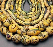 GHANAIAN POWDER GLASS BEADS of primarily adjagba types, many with cruciform decoration of powder glass and decoration from preformed elements, both indigenous and European, such as foreground bead with chevron fragments.