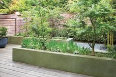 """The concrete planters were poured in place, then covered with a tinted parge coat that looks like a thick, troweled finish. """"We worked on six different color samples to get something kind like a blue-green-gray, and it has a lovely weathered finish,"""""""