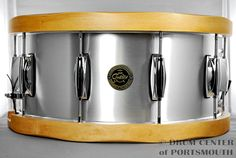 Gretsch Aluminum Snare Drum With Wood Hoops Aluminum / Wood Hoop 6.5x14 Snare Drum HEADS: Remo® USA Coated Ambassador batter head / Remo® USA Ambassador resonant headside HOOPS: 13-ply Rock maple satin natural wood hoops FEATURES: 20 strand snare wires, black nylon snare strip  Purchase Here: http://www.drumcenternh.com/drums/snare-drums/gretsch-6-5x14-alum-with-wood-hoop.html