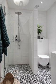 aménager une petite salle de bain, idee salle de bain petite surface, grande douche séparée du wc avec un mur en carrelage blanc, carrelage du sol en noir et blanc, motifs anciens, fleurs et plantes