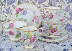 Vintage bone china tea set for two made by Royal Stafford, likely manufacture date 1940s - 1950s. The tea set consists of milk jug, sugar bowl and a pair of tea cups, saucers, tea plates. The china is white and features a pattern of hydrangea flowers in pink, lilac and white . The china is gilded to the feet of the jug, cups and bowl with further gilding to the jug and cup handles. The edges of the pieces are also gilded. The china is in excellent vintage condition free from chips, cracks…