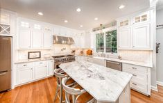 Traditional kitchen with marble counter island and white cabinets with glass pane windows