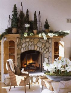 Tall wire Christmas trees add verticality to this classic stone hearth - Traditional Home®
