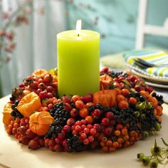 fall table centerpieces with candle, chinese lantern flowers, rowan berries and rose hips