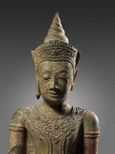 THAILANDE, Lopburi.  Statuette de bouddha en bronze à patine rouge et traces de laque or, le bras droit levé, la main manquante probablement en abhaya mudra (geste de l'absence de crainte), la coiffe surmontée d'un diadème orné de fleurs et surmonté de son chignon conique.  Il est paré de riches bijoux pectoraux.  XVIème siècle  (Accidents).  H : 50 cm