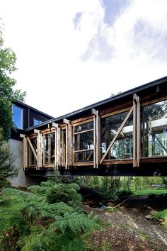 Casa Estero Puente by Aranguiz-Bunster Arquitectos (7)This house has a minimal footprint. It touches the ground with two concrete cubes with the house as a bridge in between. A small stream and beautiful ferns are under the house.