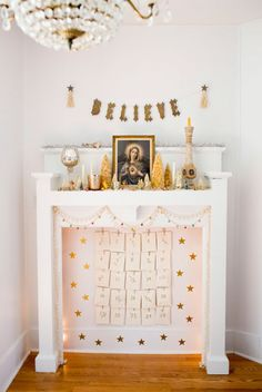 A simple garland and gold star wall decals frame the beautifully hung advent calendar. Touches of gold on top of the mantel tie everything together with decorations like candle sticks, a vintage banner, tinsel, and bottle brush trees.