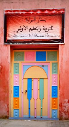 Liking the soft palette  of colors around this door with the stained stucco of the building.