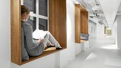 LESEPLASS hos NetLife: Her var utfordringen å gjøre en lang, smal gang til nytteareal, derfor ble eikeboksene med leselys montert på veggene. Der kan ansatte jobbe på laptoper eller for eksempel lese. Foto: Ivan Brodey