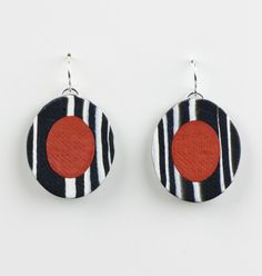 Lily Earring by Klara Borbas. The Lily Earring is bright and bold. Sculpted with rolled sheets of clay to achieve the stripes and centered by a brilliant button of red or blue clay. Dangles by silver French wire.
