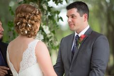 Wedding ideas: Notice the groom's red calla lily boutonniere and the bride's fantastic asymmetrical updo woven with ivory ribbon | Real Wedding in Texas Hill Country | Venue: Texas Old Town | Photographer: Rebel with a Camera