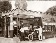 1920's station with two signs for Associated and Shell products.