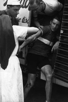A nurse treats the scraped arm of cyclist who has fallen, Tour de France, July 1939//Robert Capa