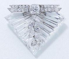 SUZANNE BELPERRON  Rare et élégant clip de revers en cristal de roche taillé, habillé d'une guirlande de diamants navettes. Monture en or et platine rehaussée d'un diamant coussin de taille ancienne en serti clos, épaulé de 2 barrettes diamantées. Il est accompagné d'une chaînette de sécurité en or gris. Vers 1934. (légers manques de matière) Poinçon de maître Groené Darde.