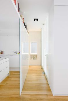Milky glass wall in kitchen. Sink at end the of the hall.