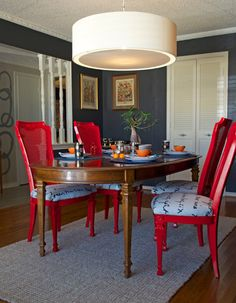 Dining room DIY painted chairs by Sarah Greenman. Red, dark walls, orange tea set, pendant equator light.